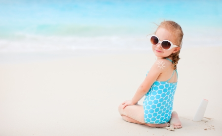 sunbathe: Little girl at beach with sun shaped cream at her back