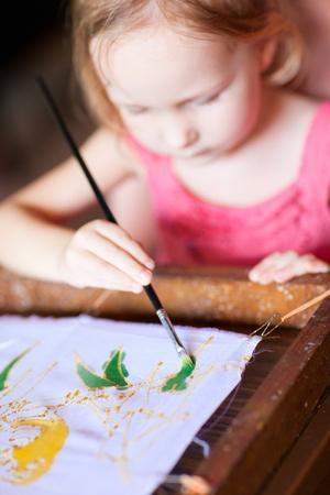 Cute little girl painting a batik, focus on paint brush photo
