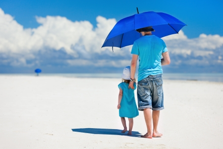 sun umbrella: Father and daughter at beach with blue umbrella to hide from the sun