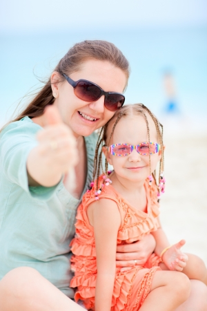 Young mother and her adorable little daughter on beach vacation photo
