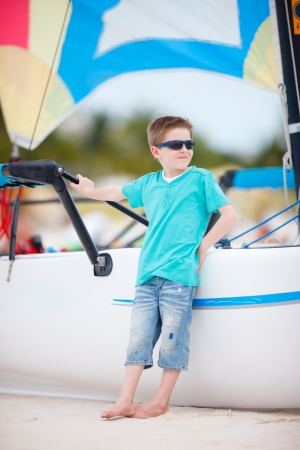 Cute boy at beach standing near catamaran Stock Photo - 14008933