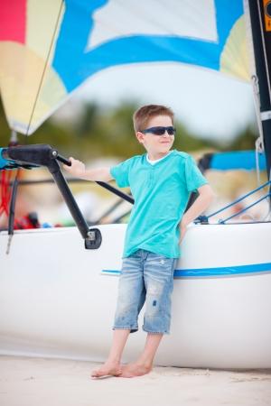 onboard: Cute boy at beach standing near catamaran