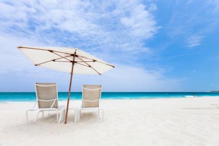 turks: Dos sillas bajo el paraguas de hermosa playa tropical en las Islas Turcas y Caicos Foto de archivo