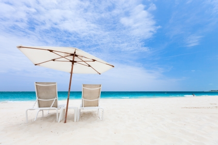 the turks: Two chairs under umbrella on beautiful tropical beach in Turks and Caicos Stock Photo