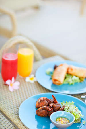 Two plates of delicious asian dishes and two glasses of fresh juices photo