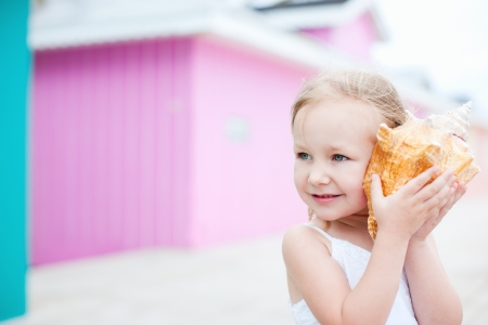 conch shell: Adorable little girl with conch shell at colorful Caribbean village Stock Photo