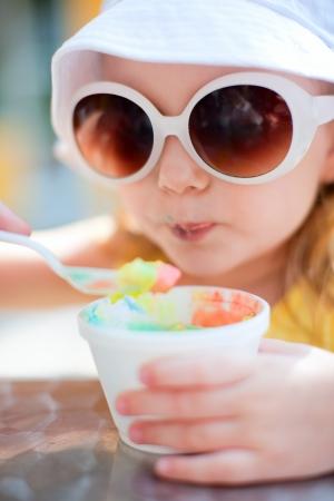 comiendo helado: Retrato al aire libre de la adorable niña comiendo un helado