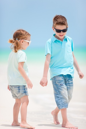 Brother and sister walking at beach photo