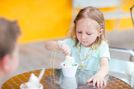 Outdoor portrait of adorable little girl eating ice cream photo