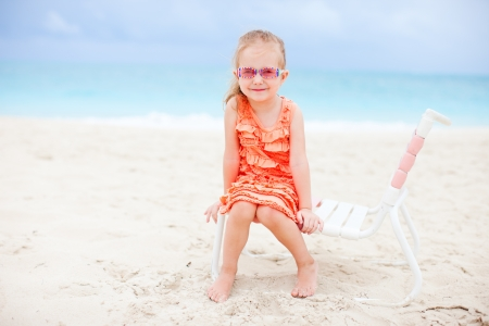 Happy little girl sitting on chair at tropical beach Stock Photo - 14157216