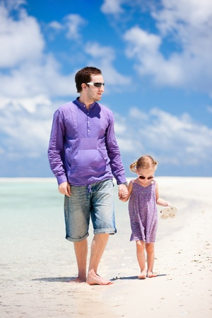 Father and his little daughter walking at beach photo