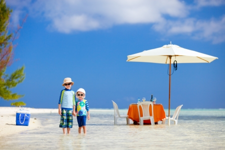 Two kids at picnic with table set in a shallow water near tropical beach photo