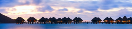 bungalows: Panorama of over the water bungalows at sunset