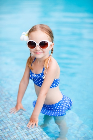 Portrait of adorable little girl at swimming pool photo