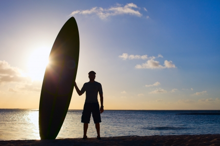 Silhouette of man holding paddle board on a beach at sunset photo