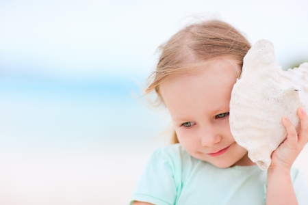 conch shell: Adorable little girl with seashell at the beach Stock Photo