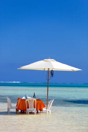 Table set for an exotic picnic in a shallow water near tropical beach photo