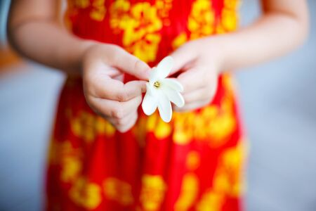 Close up of little girl holding tahitian tiare flower photo