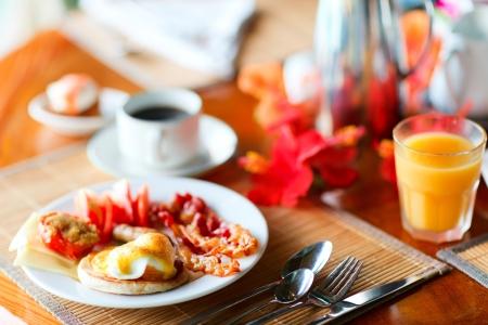 comida inglesa: Delicioso desayuno con huevos Benedict, bacon, zumo de naranja y café Foto de archivo