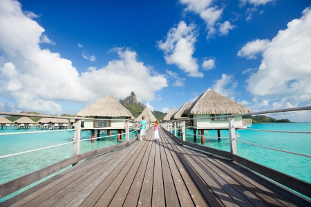 Two kids walking towards over the water bungalowas photo