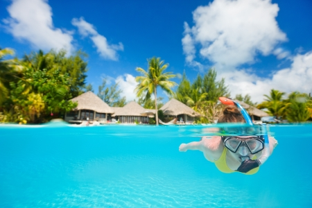 Woman snorkeling in clear tropical waters in front of exotic island photo