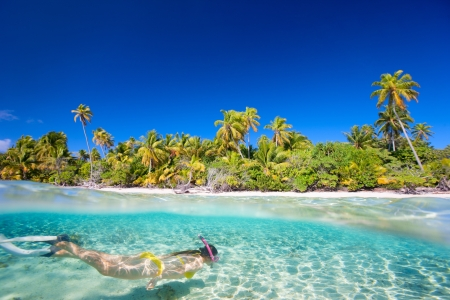 bora bora: Woman swimming underwater in clear tropical waters in front of exotic island Stock Photo