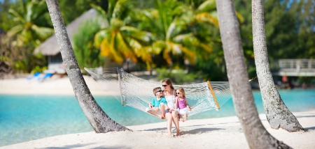 bora: Mother and two kids relaxing on hammock at tropical beach