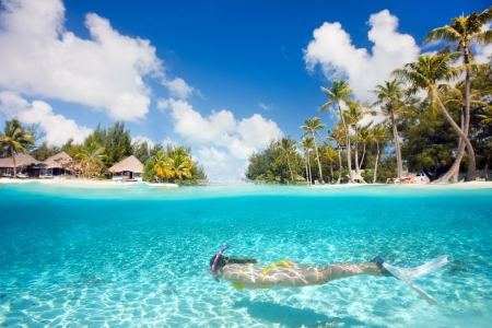 Woman swimming underwater in clear tropical waters in front of exotic island Archivio Fotografico