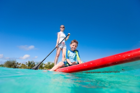 Mother and son paddling on stand up paddle board at tropical ocean Stock Photo - 15073347