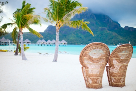 Two chairs on a beautiful beach of Bora Bora at evening photo