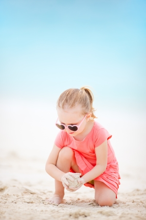Portrait of adorable little girl at tropical beach playing with sand photo