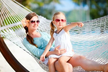 sun glasses: Mother and daughter on tropical vacation relaxing in hammock Stock Photo