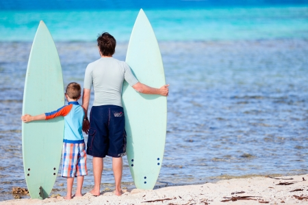 Back view of father and son with surfboards at beach photo