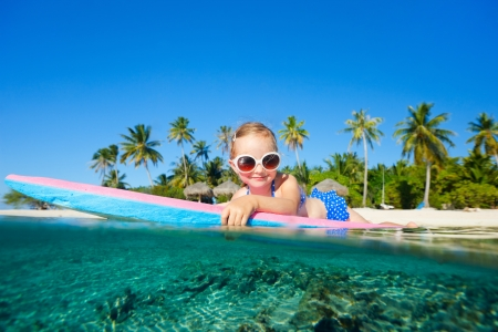 swimming at the beach: Adorable little girl on tropical vacation swimming