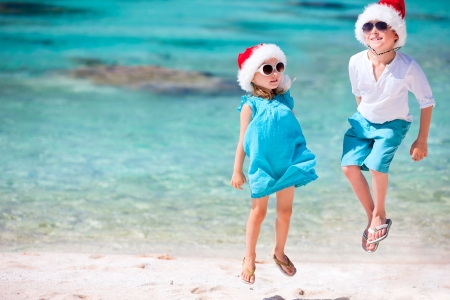 Kids in Santa hats having fun at tropical beach photo