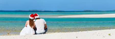 Romantic couple in Santa hats sitting on a tropical beach Stock Photo - 15288860