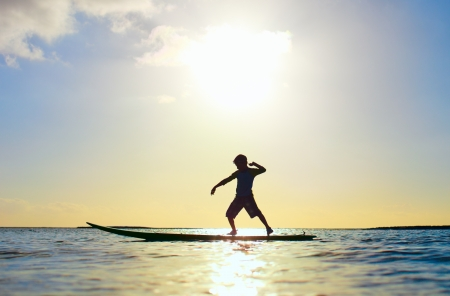 surfboard: Silhouette of little boy standing on a surfboard at sunset Stock Photo