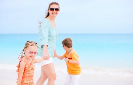 Mother and kids on Caribbean vacation walking along the beach photo