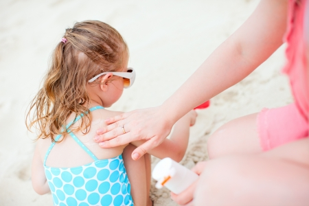 Mother applying sunblock cream on her daughter shoulder photo