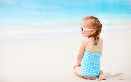 Little girl at beach with sun shaped cream at her shoulder Stock Photo