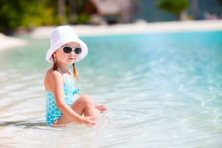Adorable little girl at shallow water on a tropical beach photo