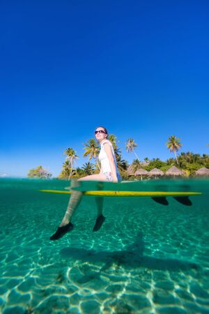 Woman sitting on a surfboard at ocean in front of tropical island