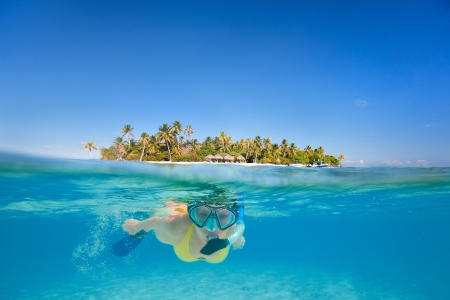 bora bora: Woman snorkeling in clear tropical waters in front of exotic island