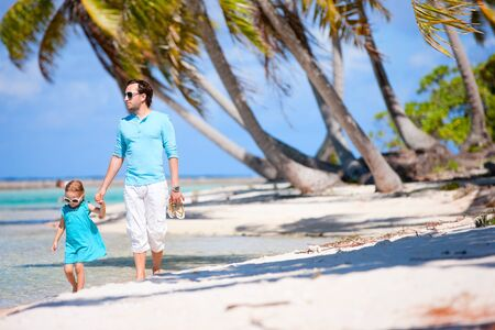 Father and daughter walking on a deserted tropical beach Stock Photo - 15421850