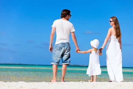 Back view of beautiful family on tropical beach photo