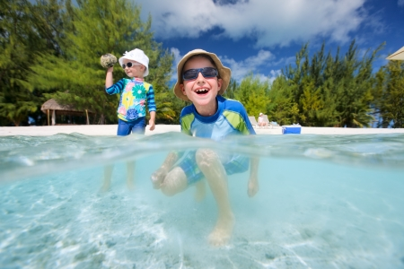 Two kids playing in shallow water in front of tropical island photo