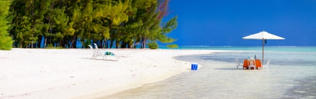 tahiti: Panoramic photo of a tropical beach with picnic table set in a shallow water