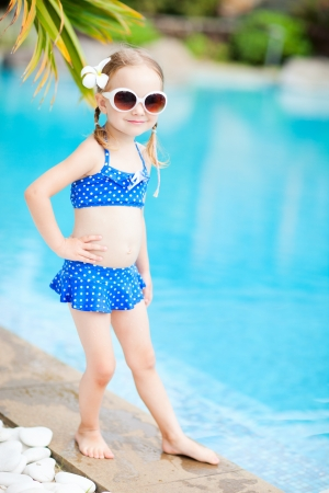 Portrait of adorable little girl standing near a swimming pool photo