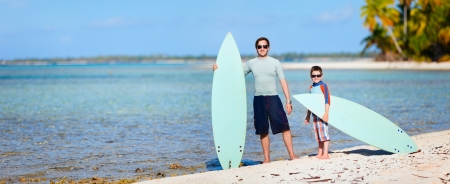 Panoramic scenery of a happy father and son with surfboards at beach photo