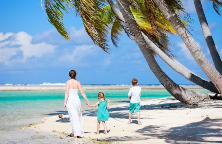 Back view of a mother walking with her two kids along a tropical beach photo